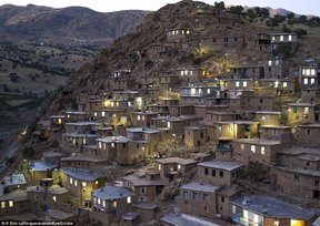 Household-lights-illuminate-the-Kurdish-village-of-Palangan-at-dusk-which-cascades-down-a-steep-hill.jpg